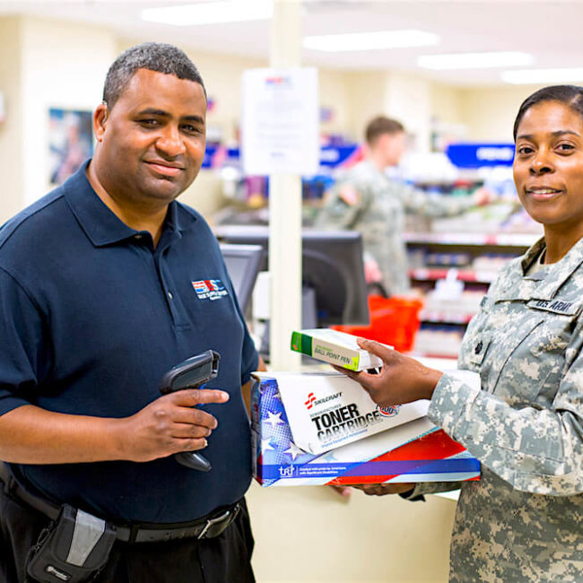 Smiling male employee selling products to a happy female military customer.