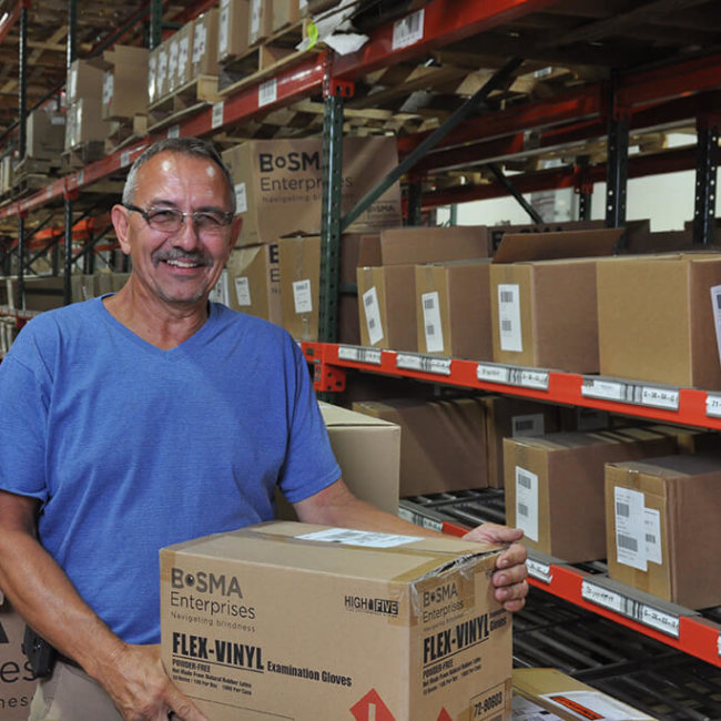 Male employee organizing boxes of products on factory floor