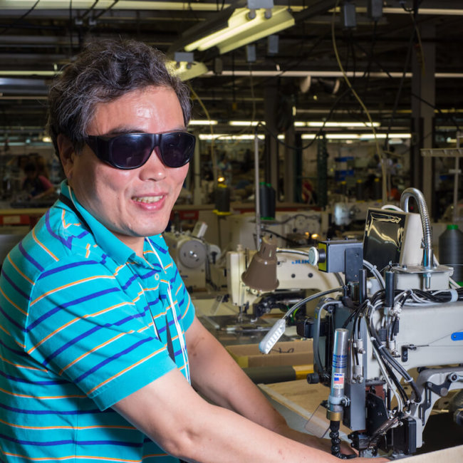 Male employee who is blind smiling as he works with machinery.