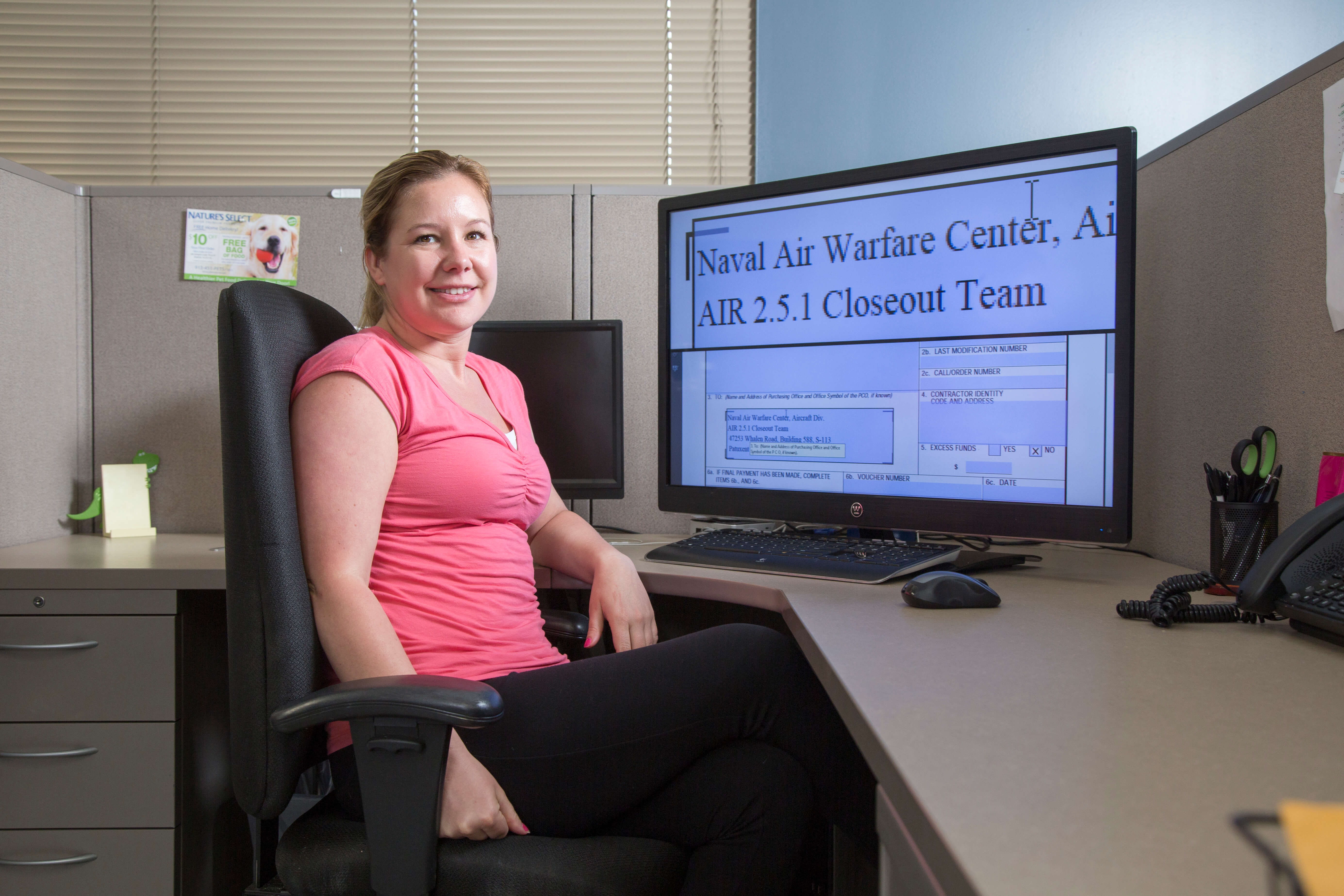 Happy female employee sitting at a computer performing CMS work
