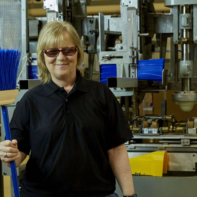 Smiling female employee holding up finished product from broom assembling machine