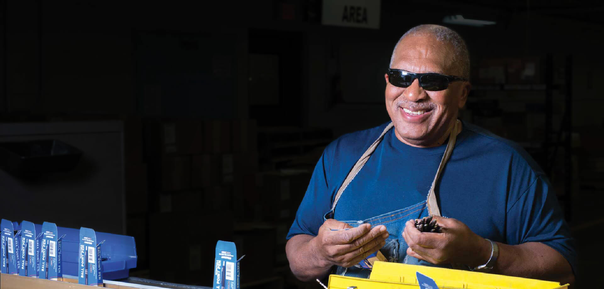 Smiling male employee putting pens into boxes at packaging station