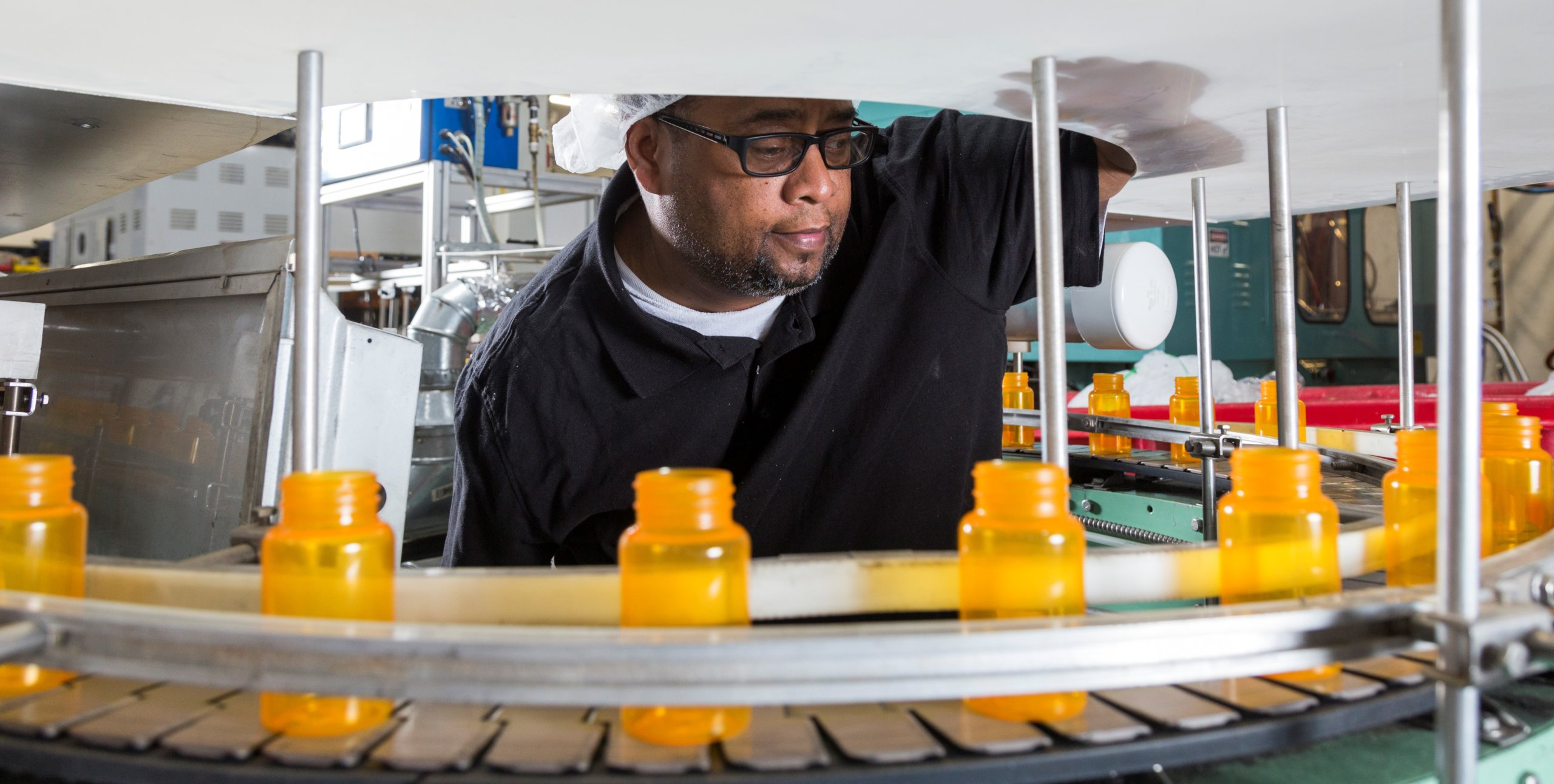A Black man in a dark shirt and glasses watches medicine bottles on a conveyor belt.