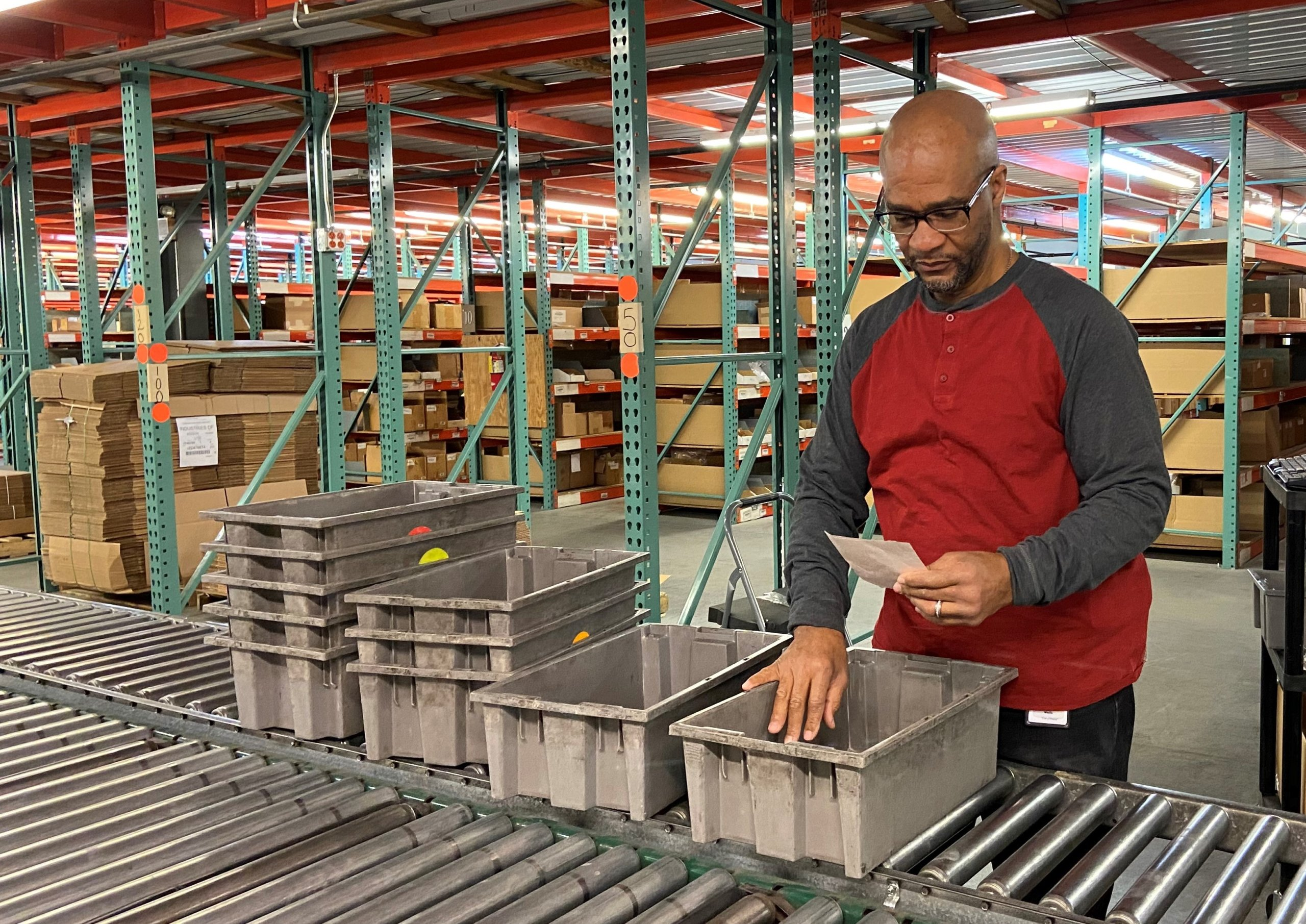 man who is visually impaired checking bins in warehouse