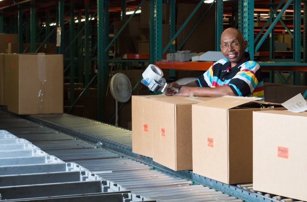 Employee who is blind packing boxes