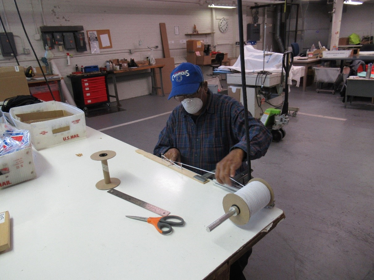 male employee who is blind wearing a mask sitting at a sewing table