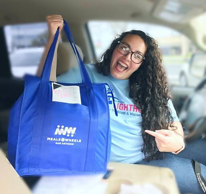 Employee from San Antonio Lighthouse for the Blind displaying a meals on wheels bag to be delivered