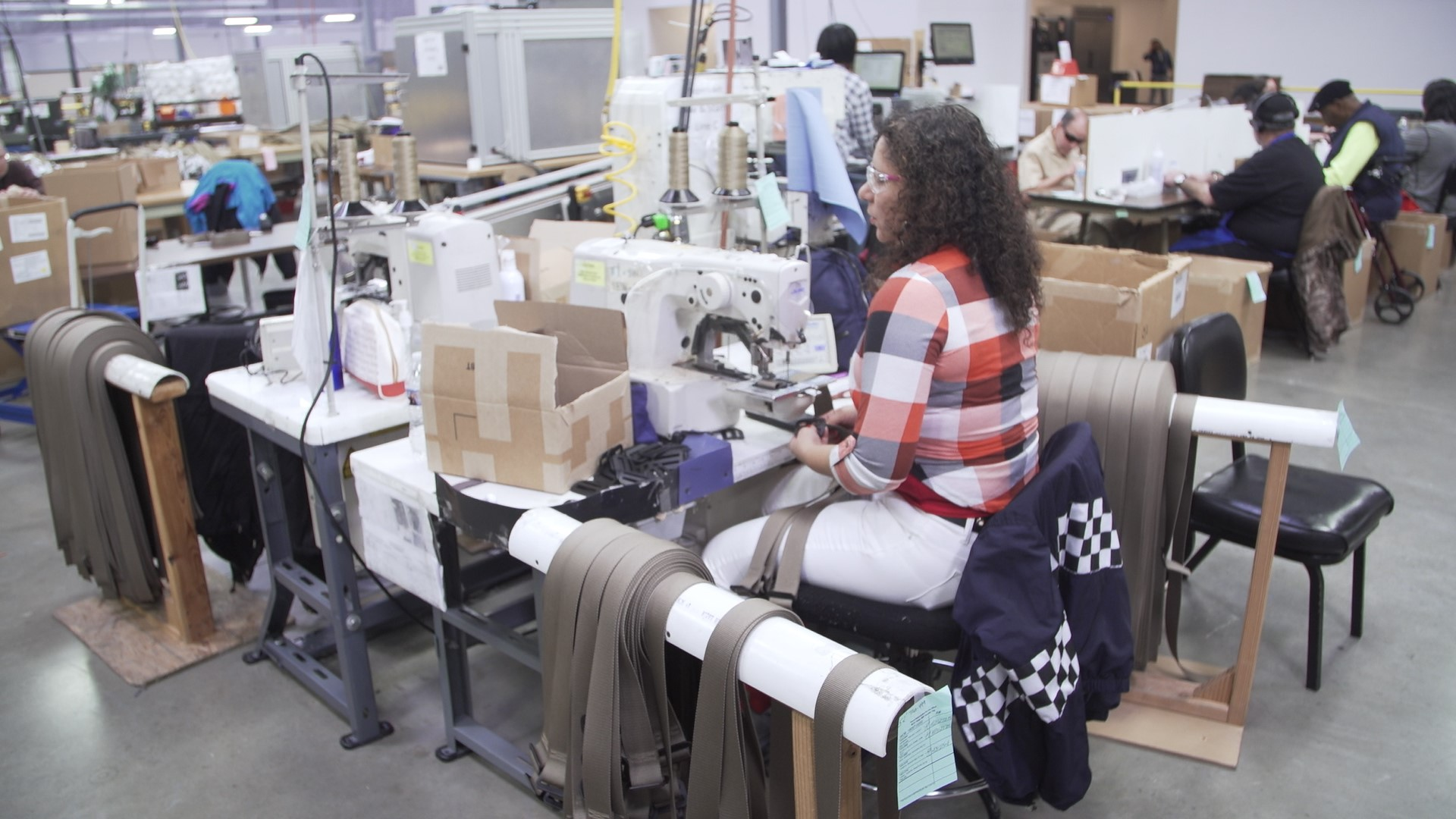 woman who is blind operating an industrial sewing machine